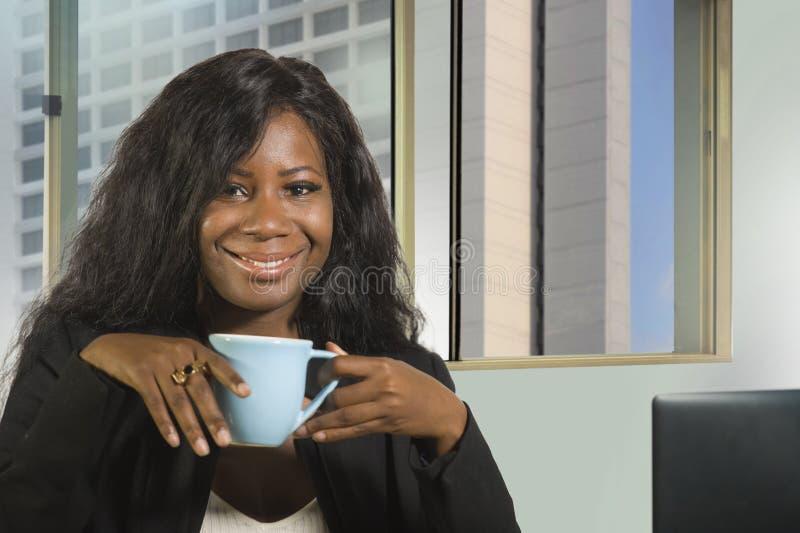 年轻愉快和有吸引力黑非裔美国人女实业家工作确信在计算机书桌饮用的咖啡微笑的satisfi 免版税库存图片