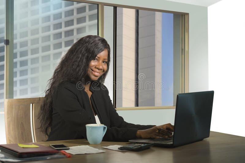 年轻愉快和有吸引力黑非裔美国人女实业家工作确信在计算机在财政满意的书桌微笑 库存图片