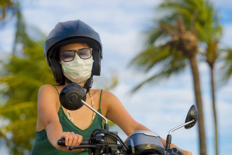 年轻愉快和相当亚洲中国妇女骑马滑行车佩带的摩托车盔甲和防护面罩在被赶走的摩托车保险柜 免版税库存图片