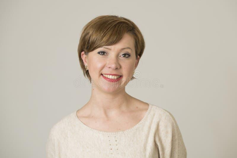 年轻愉快和相当红色头发妇女画象她的30s的在甜微笑和正面看对照相机孤立的面孔表示 免版税库存图片