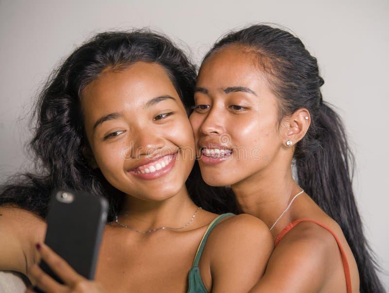 年轻愉快和美丽的亚裔姐妹或女朋友在家结合与手机的微笑的快乐的采取的selfie照片 库存照片