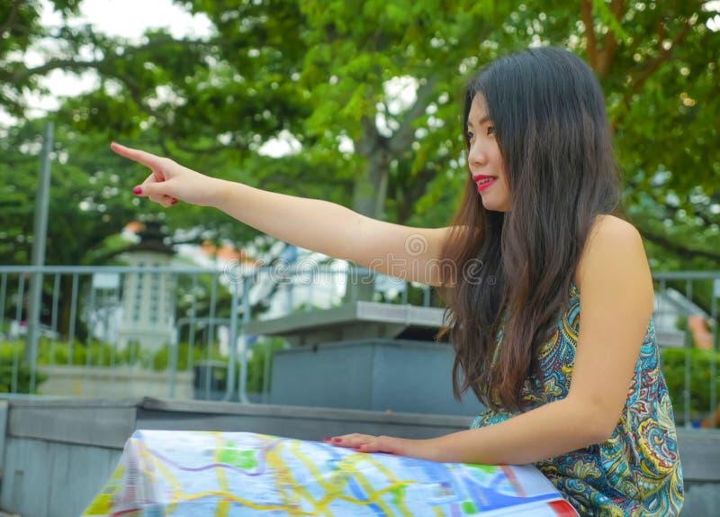 年轻愉快和美丽的亚裔韩国旅游妇女生活方式接近的画象看城市地图的街道公园的搜寻f 库存照片