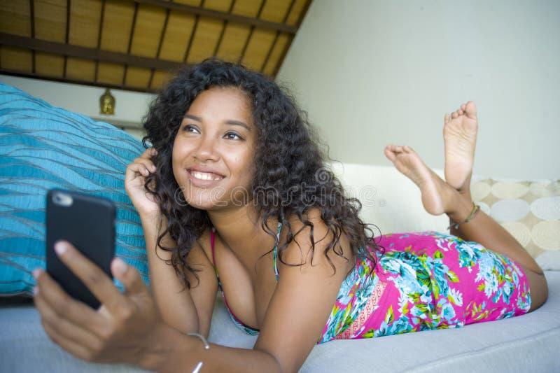 年轻愉快和美丽的黑人非裔美国人的妇女生活方式画象在家使用手机网络和te 库存照片