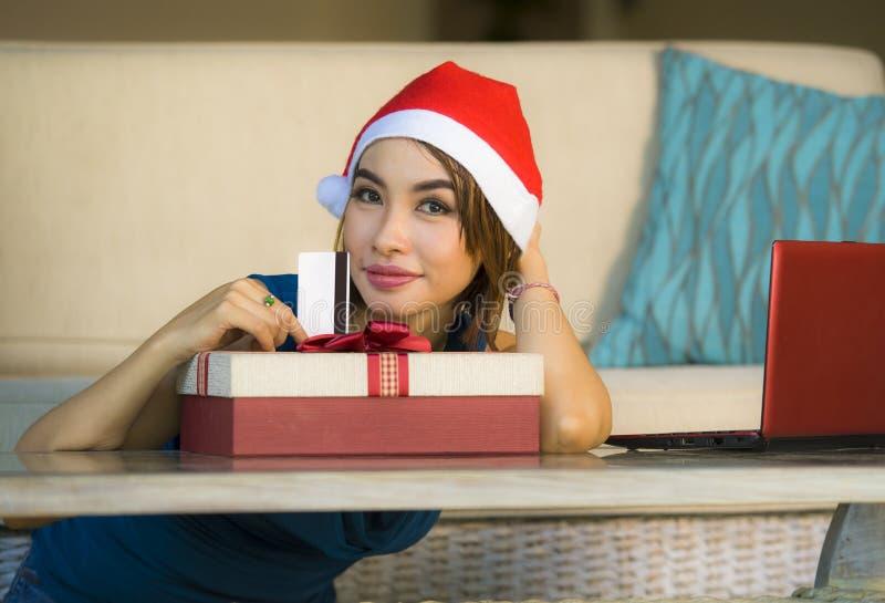 年轻愉快和美女在家放松了在圣诞老人帽子的长沙发使用支付在与信用c的圣诞礼物的手提电脑 库存照片