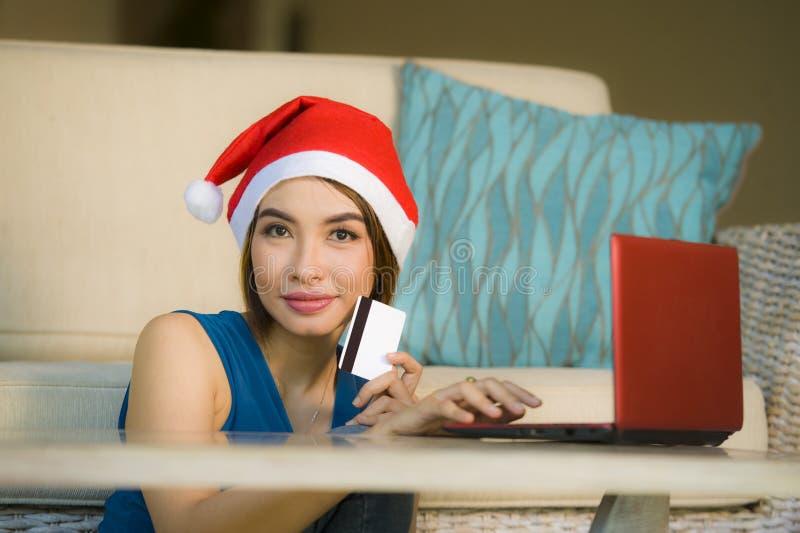年轻愉快和美女在家放松了在圣诞老人帽子的长沙发使用支付在与信用c的圣诞礼物的手提电脑 库存图片