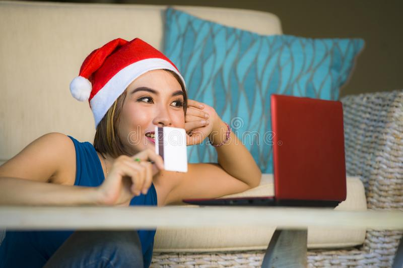年轻愉快和美女在家放松了在圣诞老人帽子的长沙发使用支付在与信用c的圣诞礼物的手提电脑 图库摄影