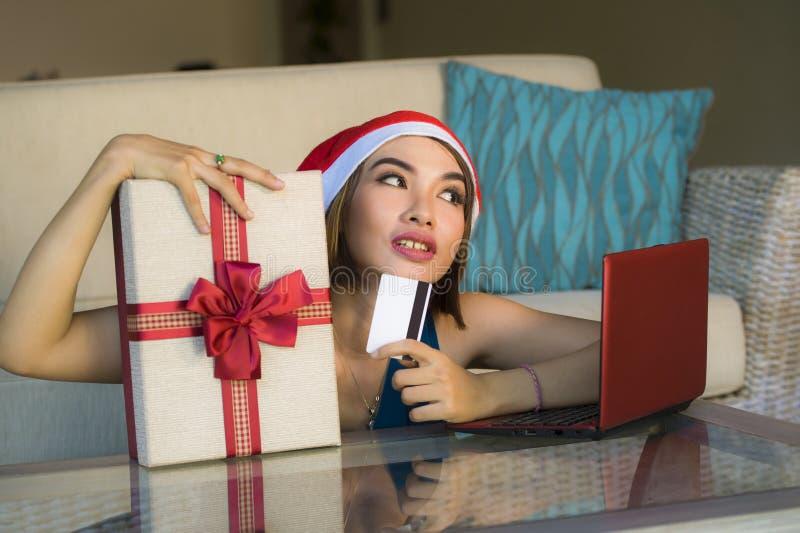 年轻愉快和美女在家放松了在圣诞老人帽子的长沙发使用支付在与信用c的圣诞礼物的手提电脑 免版税库存照片