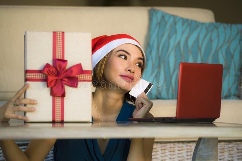 年轻愉快和美女在家放松了在圣诞老人帽子的长沙发使用支付在与信用c的圣诞礼物的手提电脑 免版税库存图片