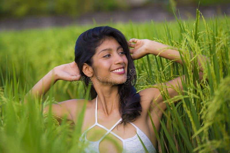 年轻愉快和美好西班牙妇女微笑嬉戏获得摆在性感的乐趣隔绝在绿色米领域在亚洲旅游旅行 免版税库存图片