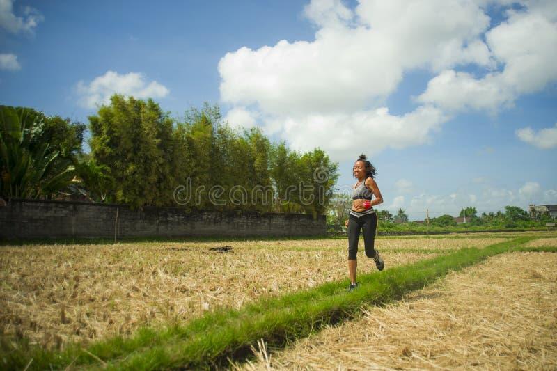 年轻愉快和适合的东南亚泰国赛跑者妇女健康生活方式画象连续锻炼的户外在绿色领域bac 免版税图库摄影