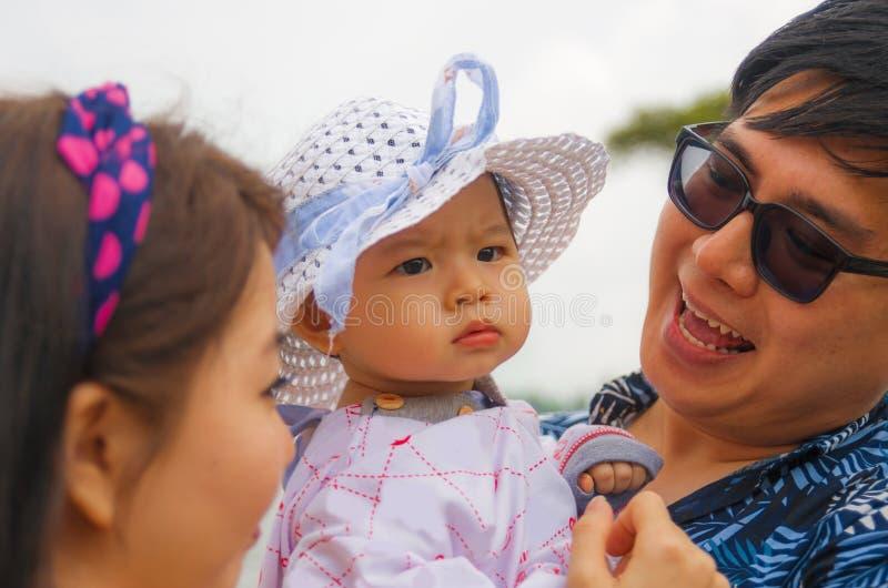 年轻愉快和骄傲的亚洲中国夫妇户外坦率的生活方式画象作为抱着可爱的女儿婴孩的慈爱的父母的 免版税库存照片