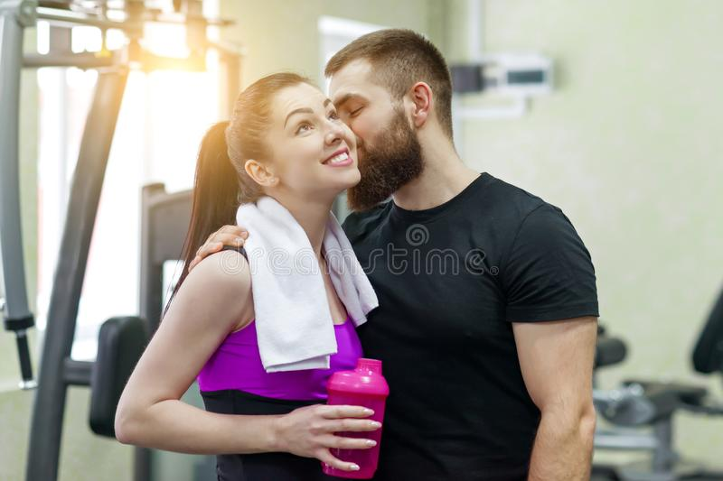 年轻愉快微笑的男人和妇女谈的拥抱在健身房 体育、训练、家庭和健康生活方式 免版税库存照片
