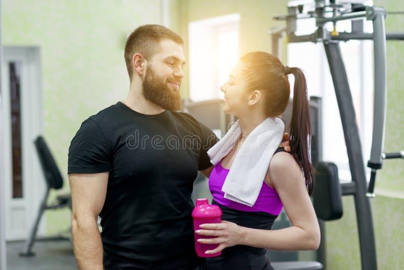 年轻愉快微笑的男人和妇女谈的拥抱在健身房 体育、训练、家庭和健康生活方式 库存图片