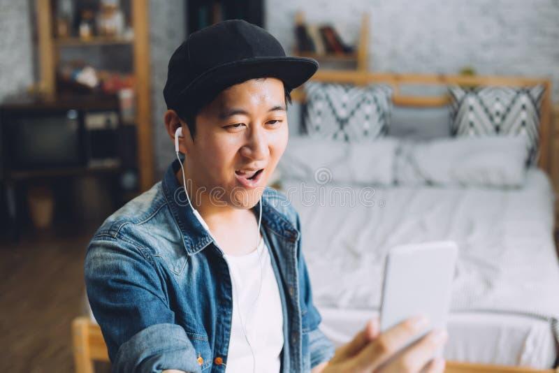 年轻愉快的亚裔人谈的录影电话通过智能手机佩带的耳机在家 库存照片
