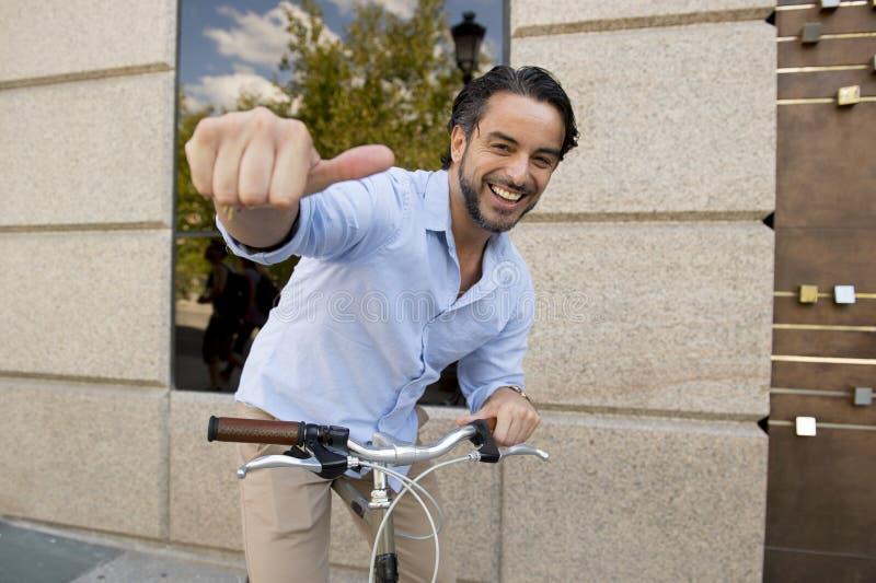 年轻愉快的人微笑的摆在凉快与葡萄酒凉快的减速火箭的自行车 免版税库存照片
