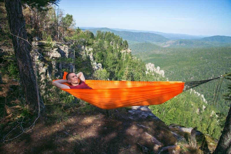 年轻愉快的人放松的在山顶部的吊床 夏天旅行生活方式 免版税库存照片