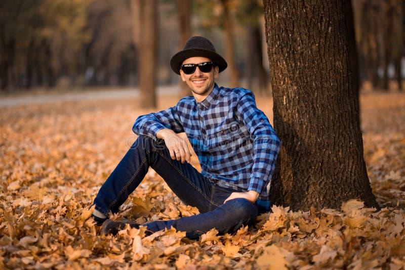 年轻愉快的人时尚室外画象有帽子和太阳镜的在秋天,减速火箭的样式颜色口气 免版税库存图片