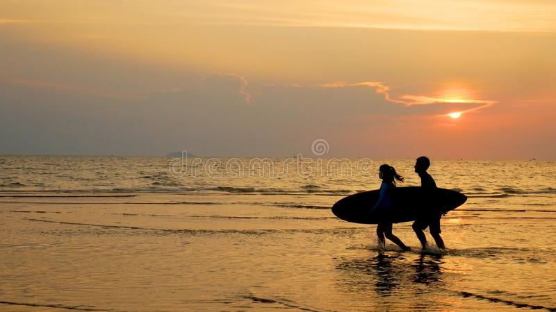 年轻愉快的人民、海浪人和女孩赛跑剪影  免版税库存照片