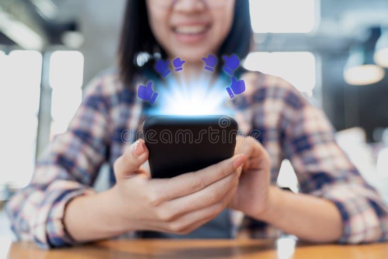 年轻愉快的使用在桌上的行家亚裔妇女智能手机在社会媒介概念的咖啡馆 millennials亚裔人民生活方式  图库摄影