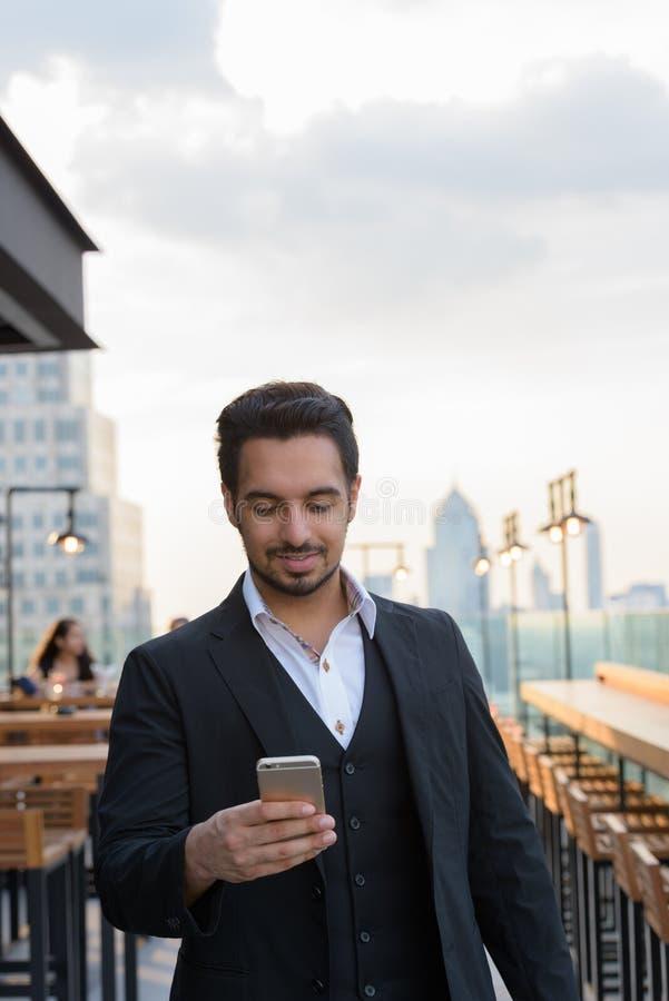 年轻愉快的印度使用手机的商人微笑的一会儿 免版税库存照片