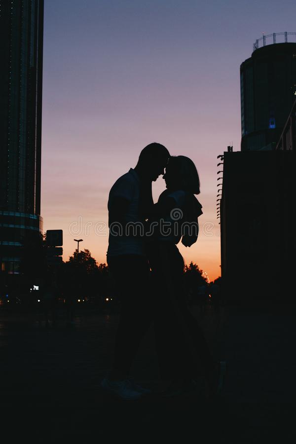 年轻愉快的夫妇剪影在亲吻在城市街道上的爱的在日落 免版税库存照片