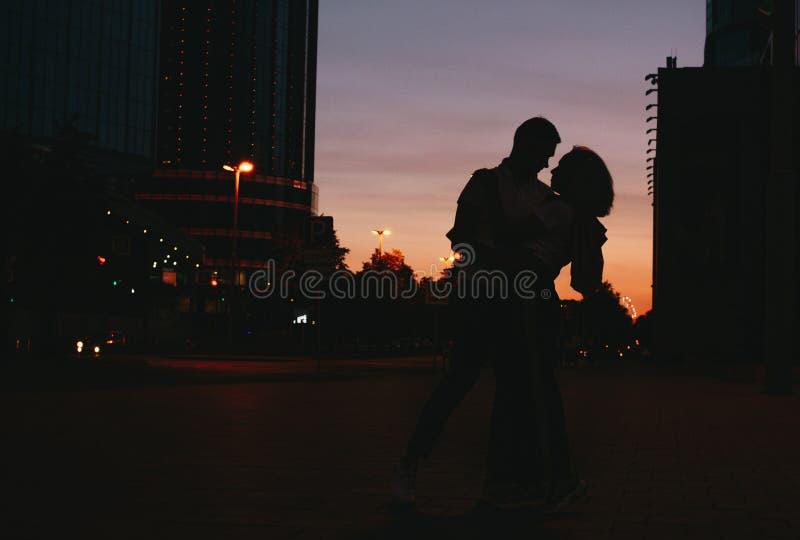 年轻愉快的夫妇剪影在跳舞在城市街道上的爱的在日落 免版税库存照片