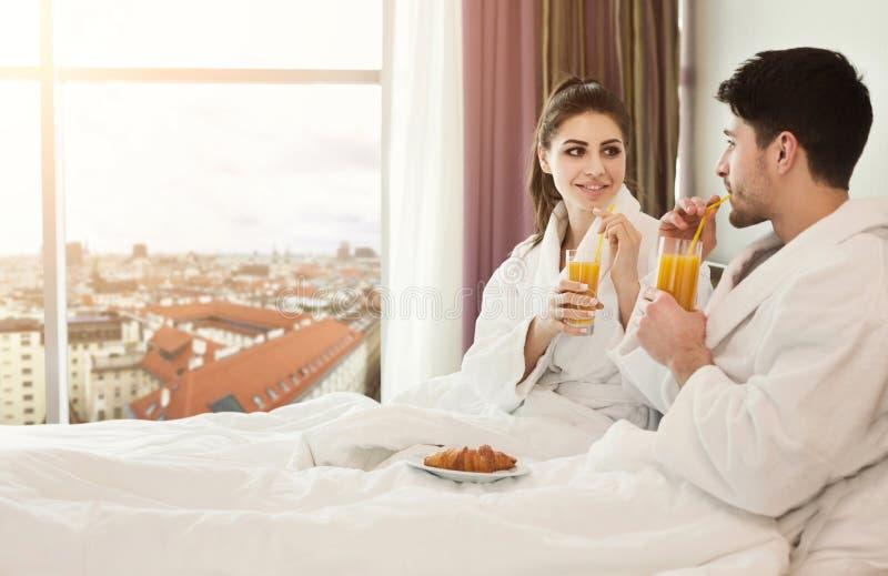 年轻愉快的夫妇吃早餐在床 库存照片