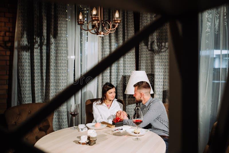 年轻愉快的夫妇浪漫日期饮料杯在餐馆的红葡萄酒,庆祝情人节 免版税库存照片