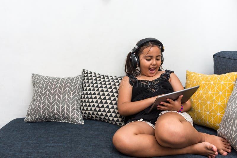 年轻愉快的女孩坐沙发使用听到与耳机的音乐的片剂 免版税库存图片