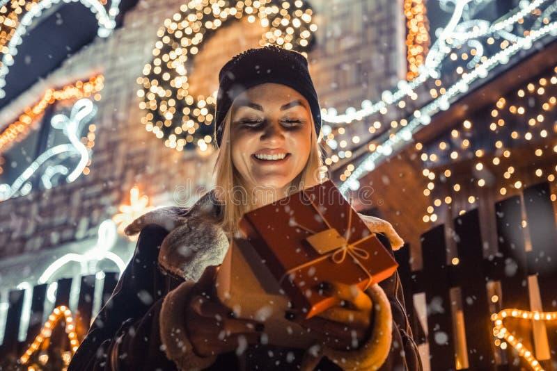 年轻愉快的女孩画象,当打开他的圣诞节礼物时 免版税图库摄影