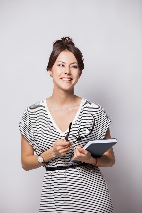 年轻愉快的女实业家在白色做在笔记薄的有些笔记,被隔绝 免版税库存图片