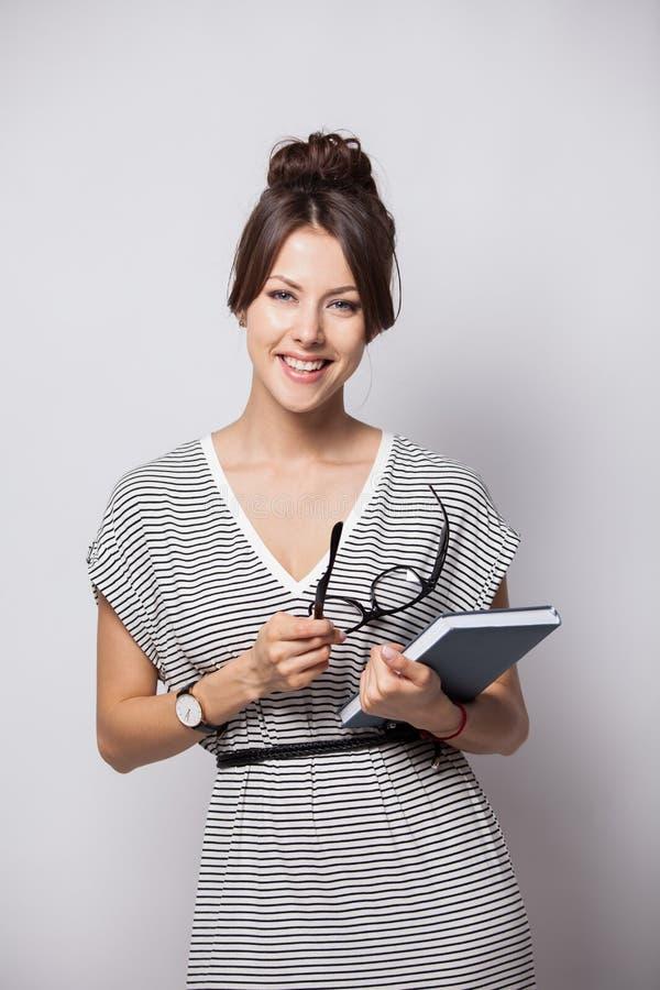 年轻愉快的女实业家在白色做在笔记薄的有些笔记,被隔绝 库存照片