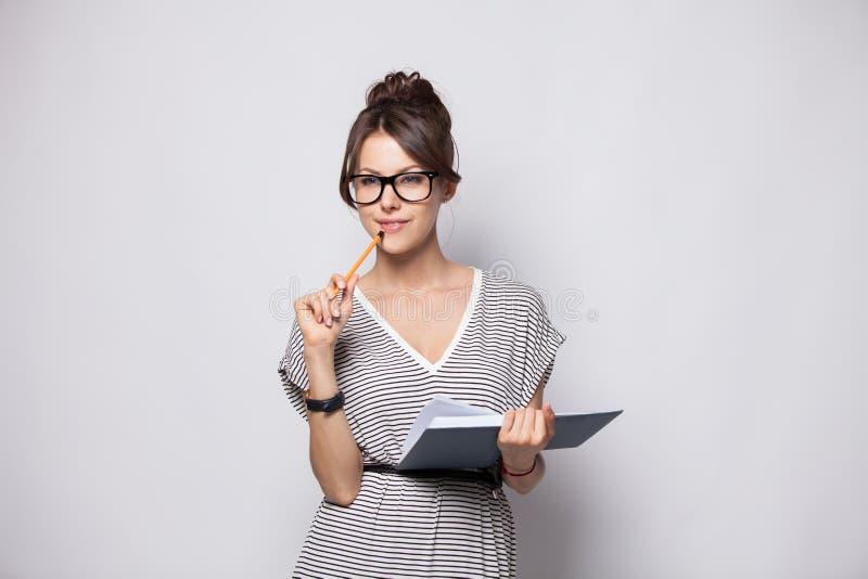 年轻愉快的女实业家在白色做在笔记薄的有些笔记,被隔绝 库存图片