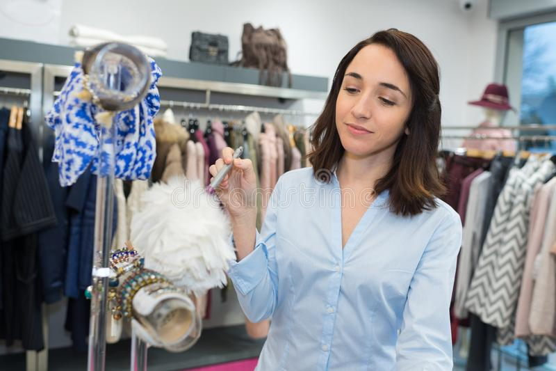 年轻愉快的女性工作在衣裳商店 免版税库存图片