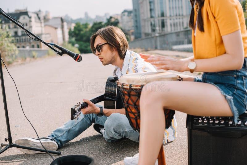 年轻愉快的女性鼓手和男性吉他弹奏者 库存图片