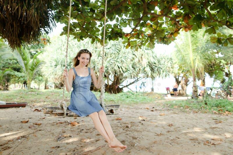 年轻愉快的妇女佩带的牛仔裤在背景中穿戴和乘坐在摇摆,沙子 免版税图库摄影