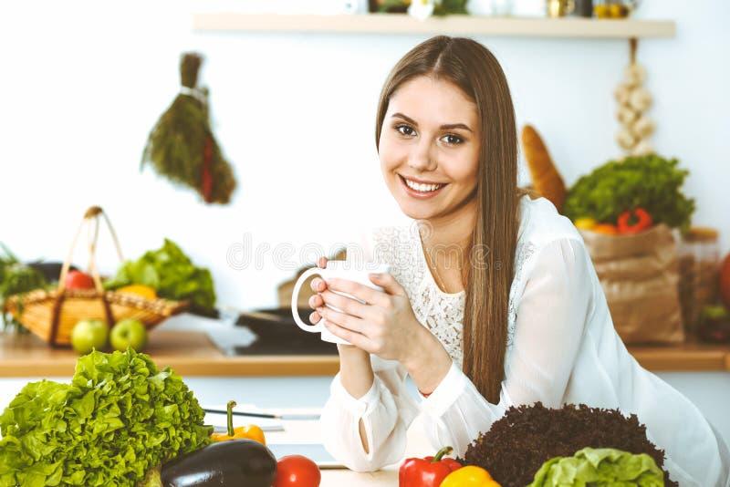 年轻愉快的妇女在厨房里拿着白色杯子并且看照相机,当坐在木桌上在中时 免版税图库摄影