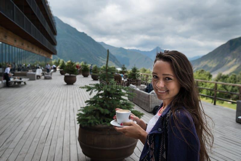年轻愉快的妇女在旅馆的大阳台站立有咖啡的 免版税库存照片