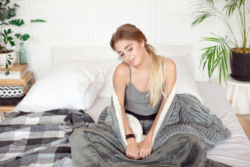 年轻愉快的妇女坐在温暖的大气的白色毯子早晨包裹的床 库存图片