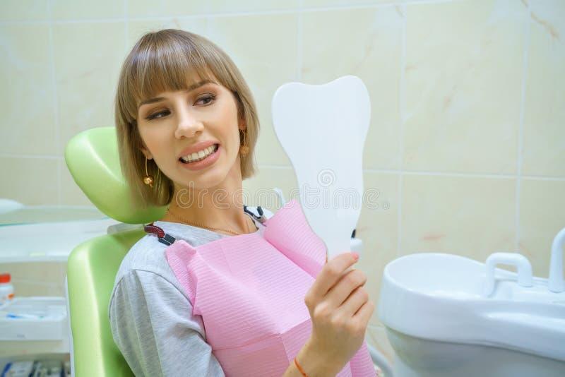 年轻愉快的妇女坐在牙医的办公室的,健康牙 免版税库存图片