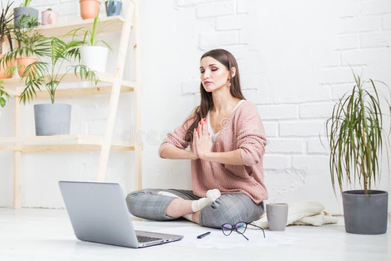 年轻愉快的妇女坐在瑜伽姿势的地板在一栋明亮的公寓并且在膝上型计算机,自由职业者女孩后工作 图库摄影