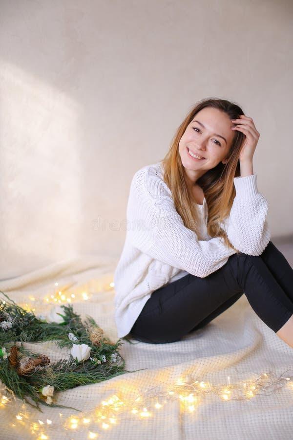 年轻愉快的妇女坐床近的花圈和黄色诗歌选 免版税库存图片