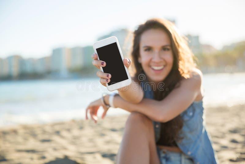 年轻愉快的妇女坐显示智能手机的海滩 库存照片