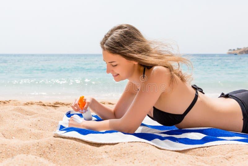 年轻愉快的妇女基于毛巾在海附近并且保护她的在手上的皮肤有遮光剂的免受浪花 免版税库存图片