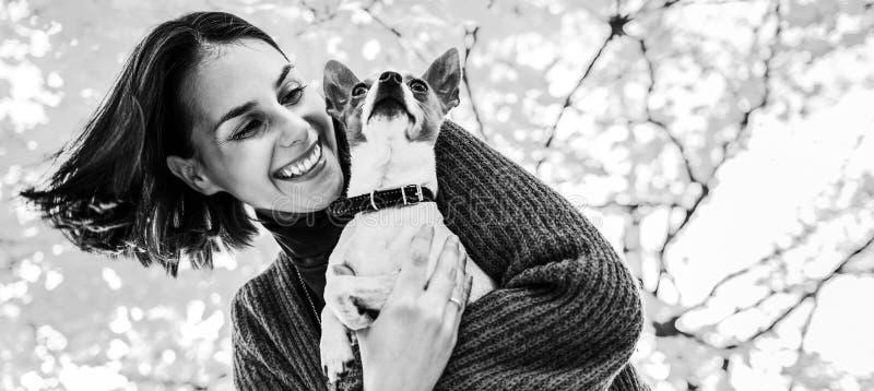 年轻愉快的妇女画象有小的逗人喜爱的狗的在公园 免版税库存图片