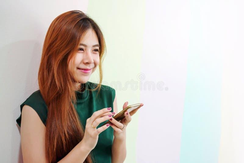 年轻愉快的妇女画象,女性使用智能手机和微笑 免版税库存照片