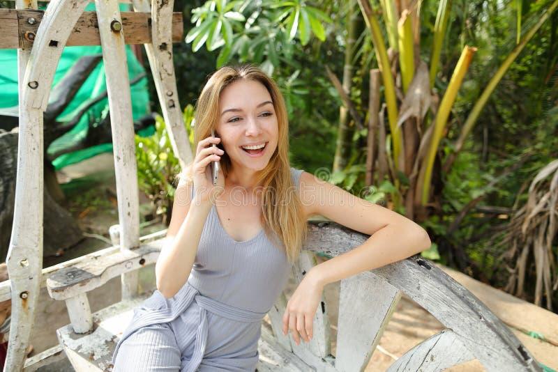 年轻愉快的妇女谈话由有棕榈的智能手机在背景中,坐摇摆 库存照片