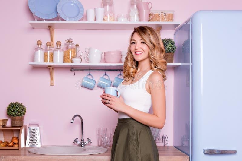 年轻愉快的妇女饮用的咖啡或茶在家在厨房里 白肤金发的美女吃她的早餐在去前 免版税库存图片