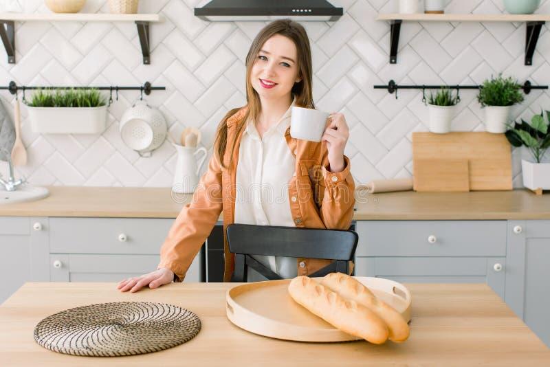 年轻愉快的妇女饮用的咖啡或茶在家在厨房里 美女吃她的早餐在去前 免版税库存照片
