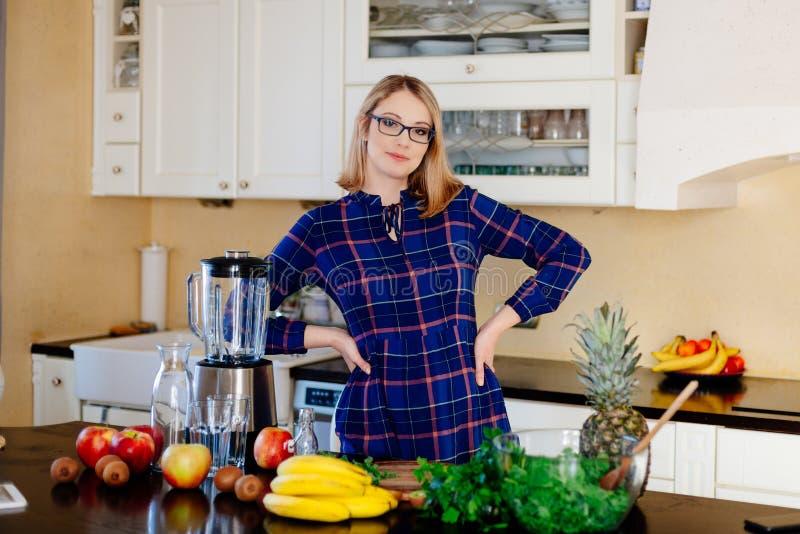 年轻愉快的孕妇健康烹调在厨房里 免版税图库摄影